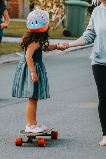 Little girl getting help from her mum while learning to ride a skateboard