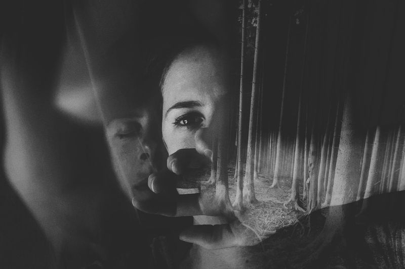 Double exposure of woman and trees in forest