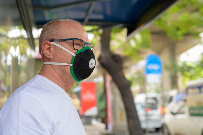 Portrait of man wearing mask in city