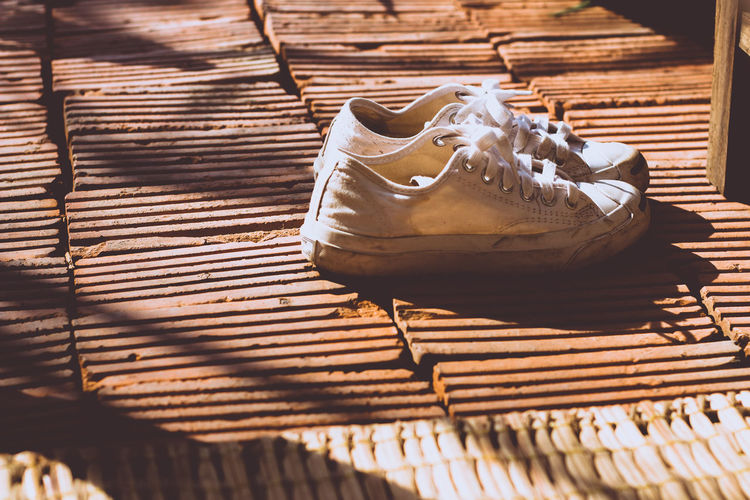 Chiang Mai | Thailand Converse Abandoned Brick Brown Canvas Shoe Close-up Contrast Day Evening High Angle View Nature No People Old Pair Pattern Shadow Shoe Shoes Sneakers Still Life Sunlight Textured  Warm Colors Wood - Material