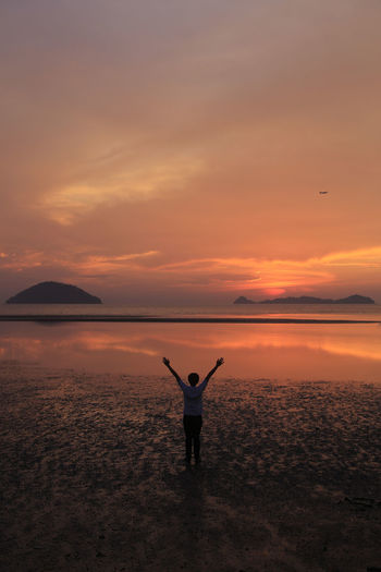 Arms Outstretched Arms Raised Beauty In Nature Horizon Over Water Human Arm Human Limb Leisure Activity Lifestyles Limb One Person Orange Color Real People Rear View Scenics - Nature Sea Sky Standing Sunset Tranquil Scene Tranquility Water