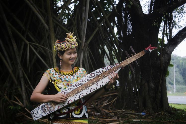 Smiling woman playing traditional musical instrument against trees
