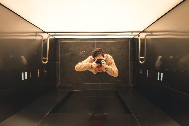 Directly above shot of man photographing with digital camera in elevator