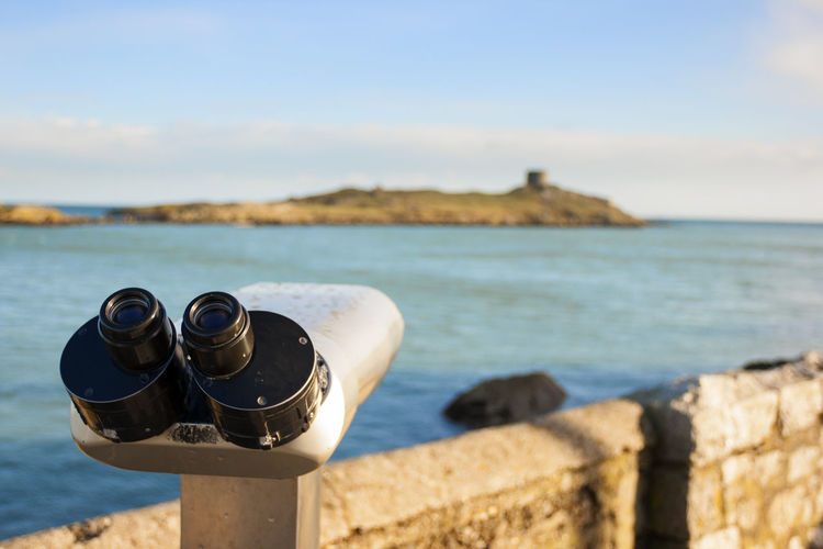 Close-up of coin-operated binoculars at beach against sky
