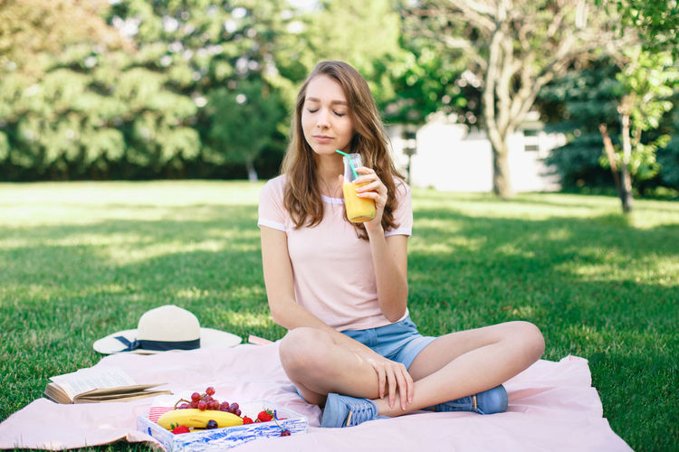 Young woman holding drink while sitting over picnic blanket on grass