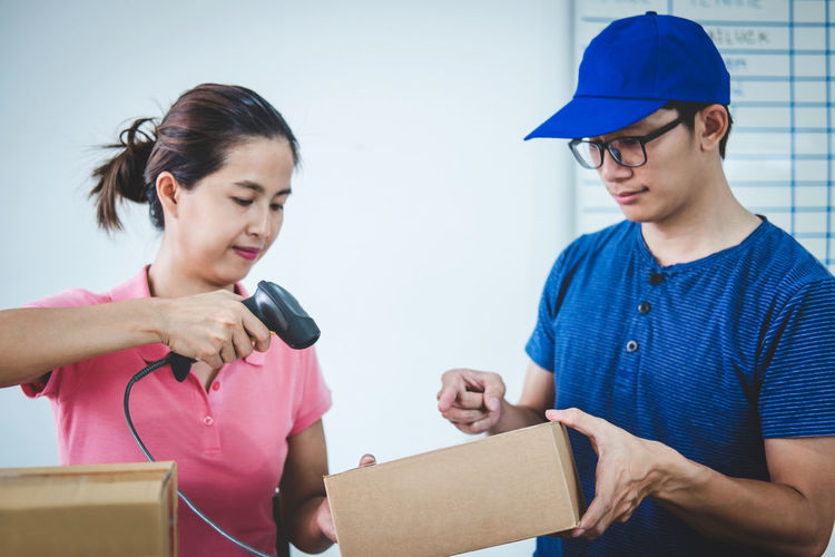 Businesswoman scanning while colleague holding box