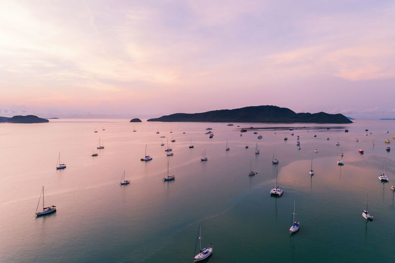 High angle view of sailboats in sea at sunset