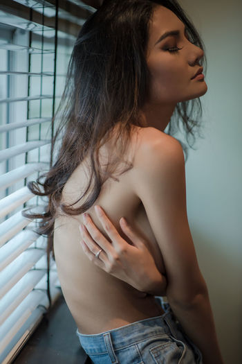Side view of beautiful shirtless young woman standing by window