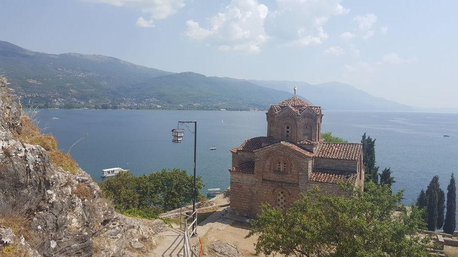 Church on hill by lake ohrid against sky