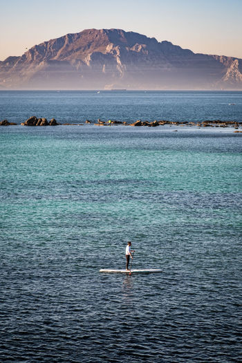 Scenic view of sea by mountain against sky. paddlesurf strait of gibraltar.