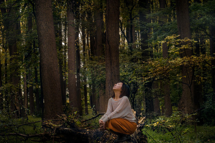 Woman looking up when sitting in forest
