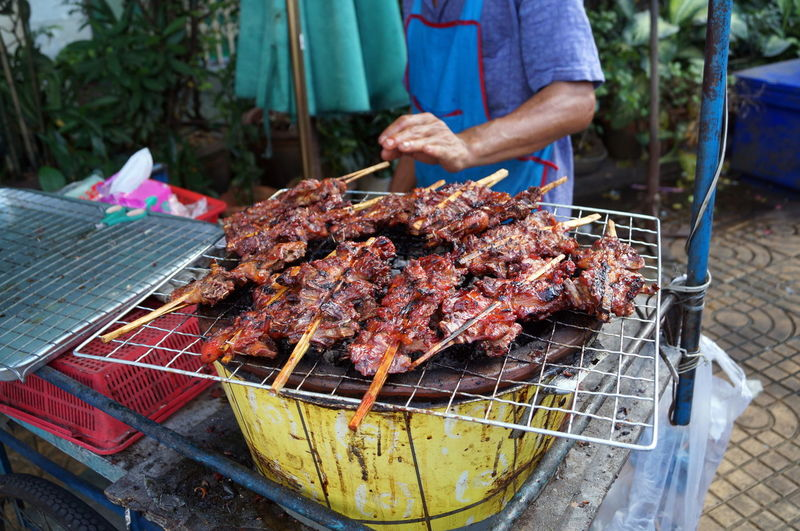 Midsection Of Man Grilling Meat On Barbecue