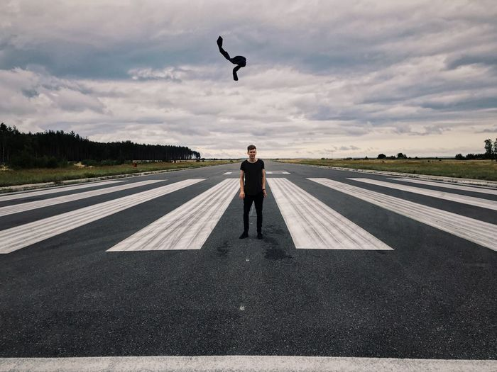 Man Standing On Airport Runway Against Cloudy Sky
