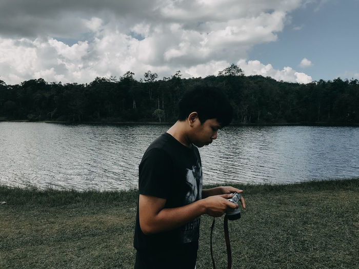 Side view of man holding camera standing by lake against sky