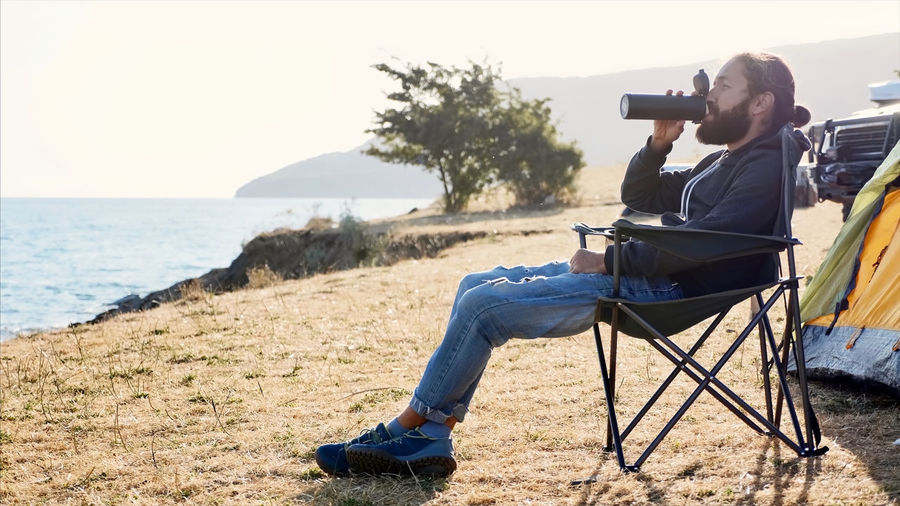 Full length of man photographing while sitting on beach