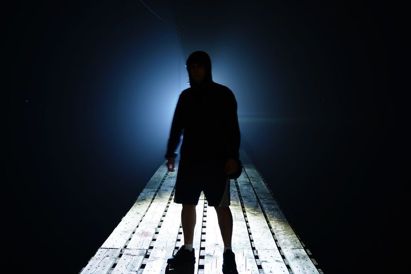 Man standing on footbridge at night