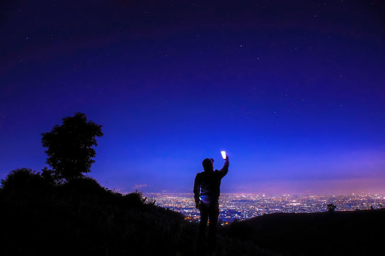 Rear view of silhouette man taking selfie on mountain against blue sky at night