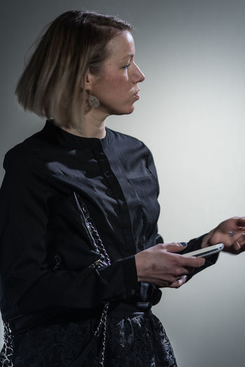 Mid adult woman using mobile phone against gray background