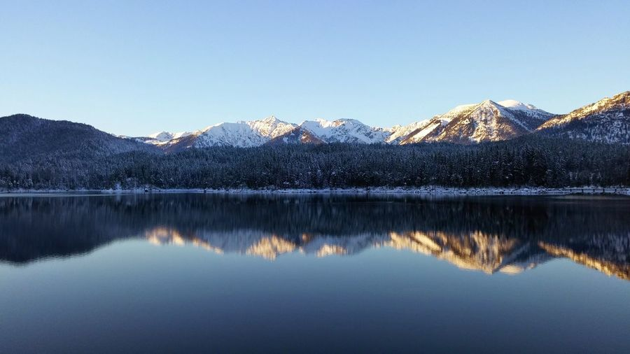 Mountains reflecting on calm lake during winter