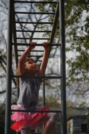 Girl climbing on monkey bars against sky