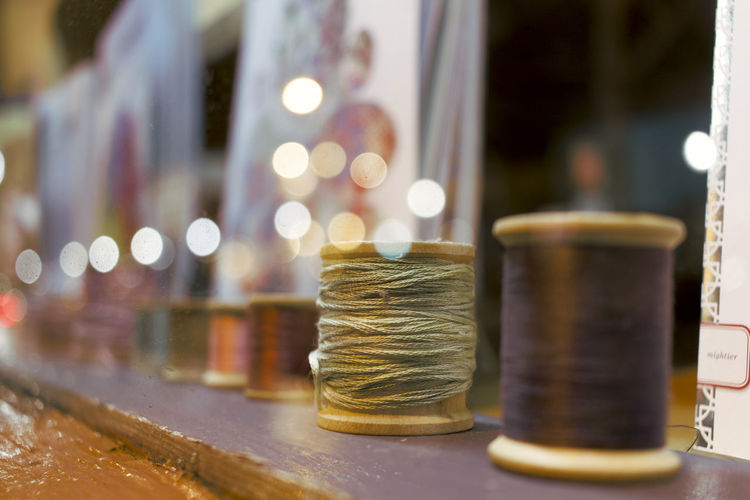 Close-up of thread spools on table at workshop