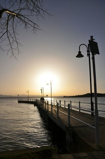 Sea Sunset Water Tradition Outdoors Travel Destinations Vacations Landscape Tranquility Silhouette Beach Horizon Over Water No People Nature Bridge - Man Made Structure Bird Palm Beauty In Nature Day Trasimenolake