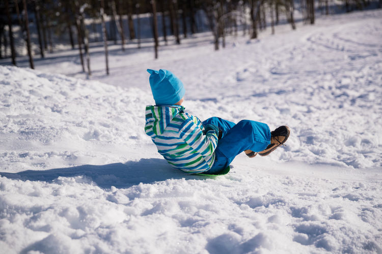 Rear view of boy on snow covered land