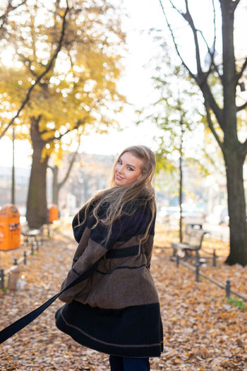 Portrait of smiling young woman standing against trees during autumn