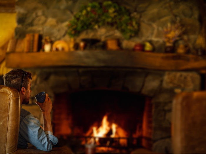Man having drink while sitting by fireplace at home