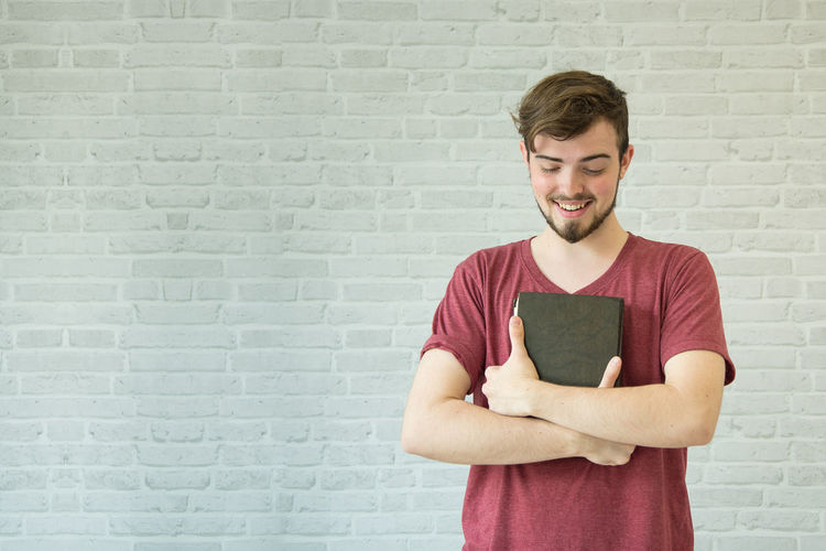 Smiling young man holding bible while standing against brick wall