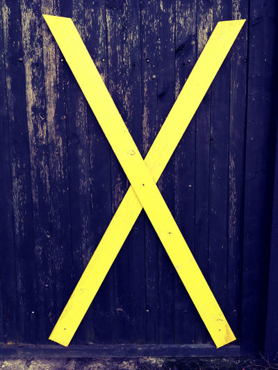 Full frame shot of yellow arrow sign on wooden wall