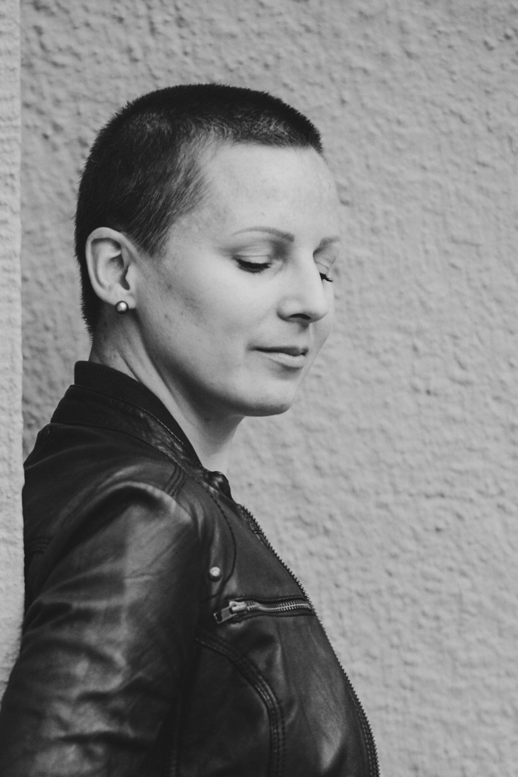 one person, real people, portrait, young adult, lifestyles, headshot, wall - building feature, jacket, casual clothing, leisure activity, clothing, leather, leather jacket, standing, looking, looking away, smiling, young women, contemplation, beautiful woman, hairstyle