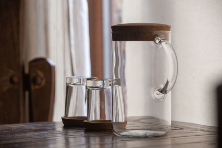 Close-up of drinking glasses with jug on table