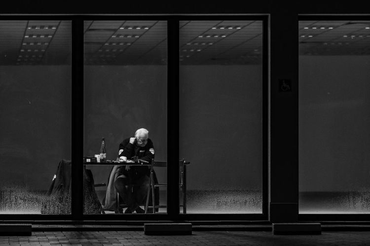 The Guardian of Nothingness. [22/365] 2016.10.31. I encountered a security guard guarding an empty office space during my late night walk in the nearby district. Black And White Candid Desk Elderly Guard Guardian Indoors  Men Monochrome One Person People Real People Security Guard Sitting Sitting Alone Store Storefront Street Street Photography Streetphotography Table Window
