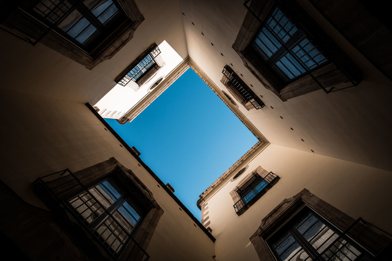 architecture, built structure, low angle view, building exterior, building, window, sky, no people, residential district, city, nature, day, directly below, outdoors, tall - high, clear sky, apartment, sunlight, city life, balcony, skylight
