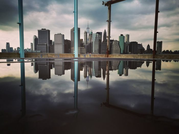 Manhattan skyline reflection in puddle at brooklyn bridge park
