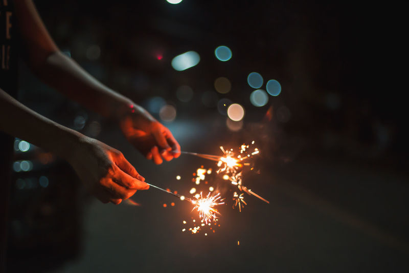 Cropped hand holding sparklers at night