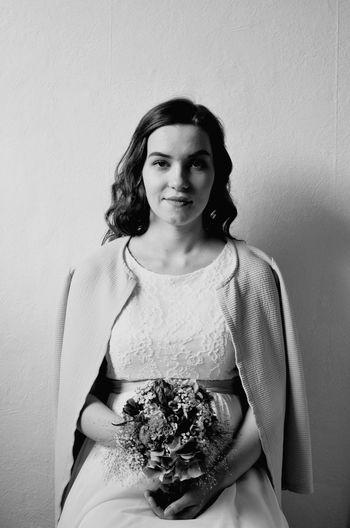 Portrait Of Bride Holding Bouquet Against Wall