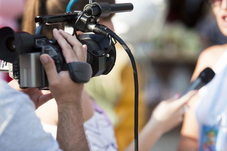 Journalist filming woman