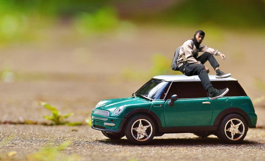 Man with toy car on road in city