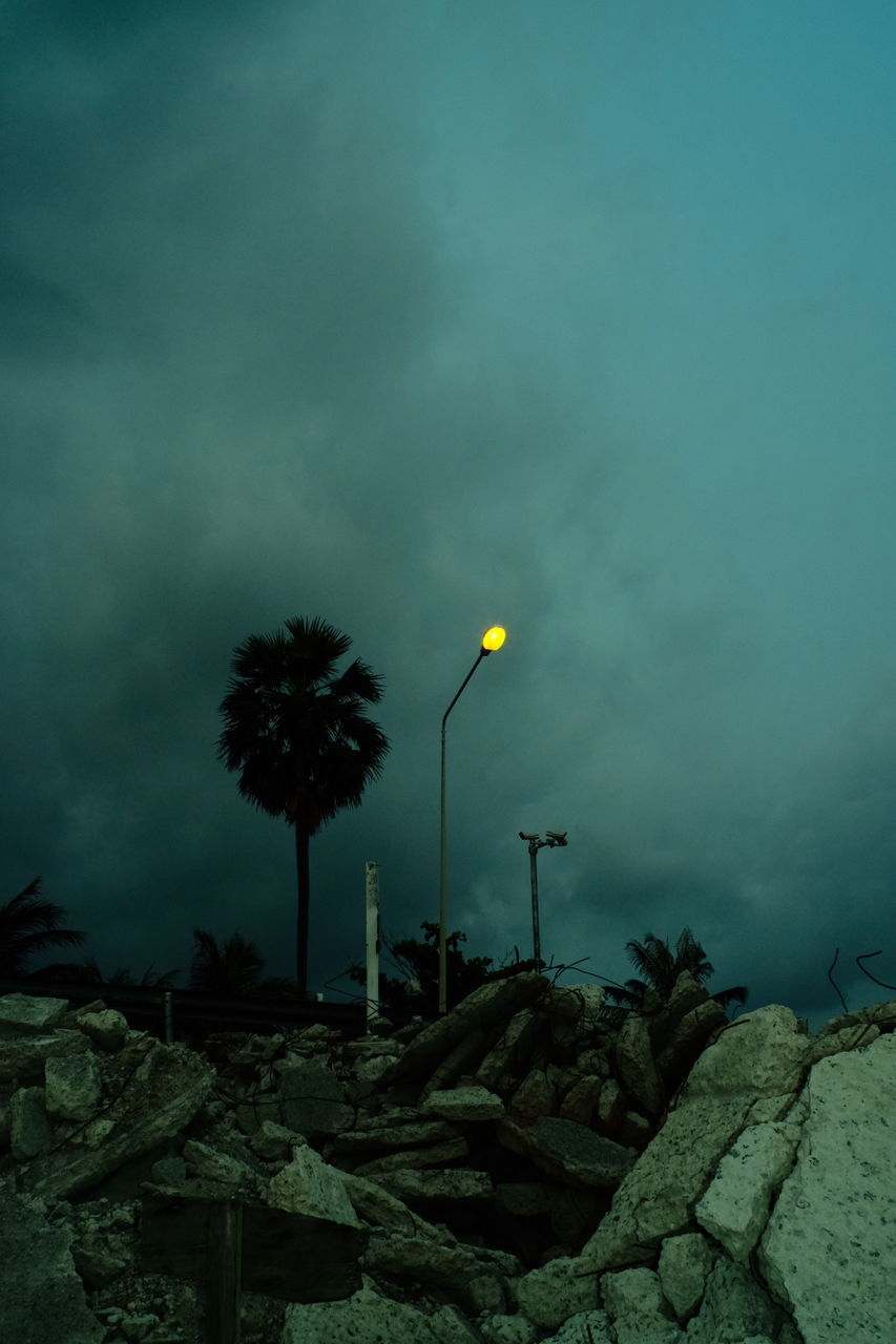 LOW ANGLE VIEW OF ILLUMINATED STREET LIGHTS AGAINST SKY AT DUSK