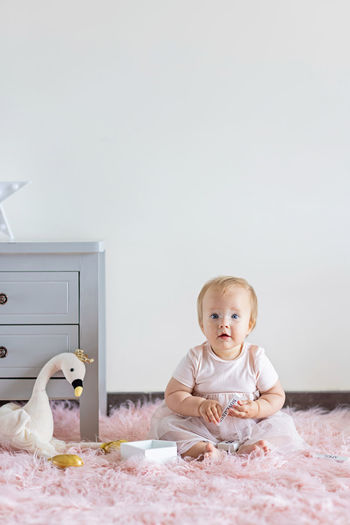 Little caucasian baby girl ten months old playing with wooden toys at home or nursery.