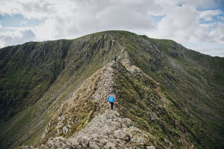Men hiking on mountain against cloudy sky