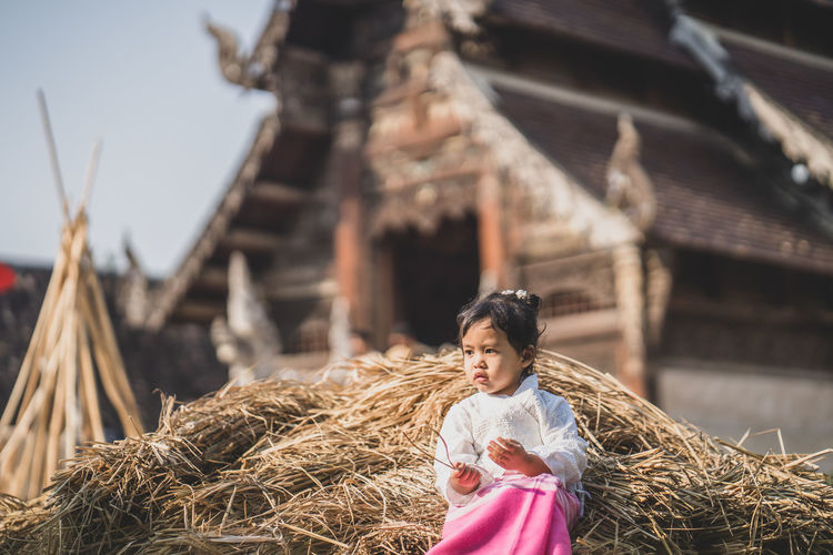 Girl sitting on haystack against cottage outdoors