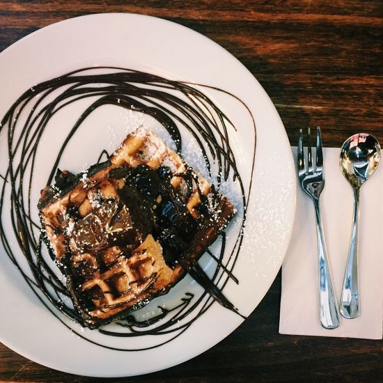 High Angle View Of Chocolate Waffle In Plate Served On Table