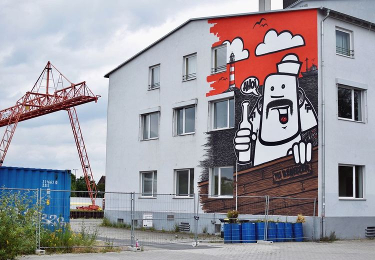 Graffiti on building by street against sky