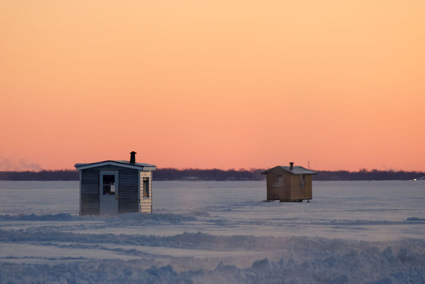 Isolated ice fishing huts on a frozen lake at sunset. Clear Sky Frozen Frozen Lake Golden Sunset Ice Fishing Winter Frozen Nature Ice Fishing Huts Ice Fishing Huts On Frozen Lake At Sunset Shacks Snow Sunset Sunset In Winter