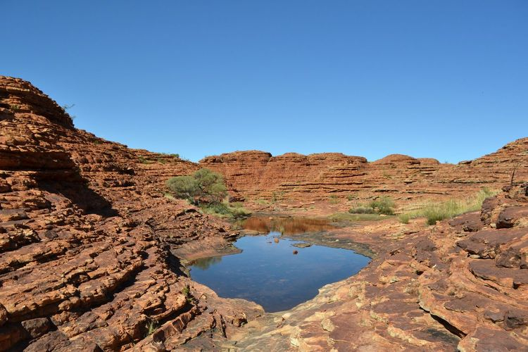 Scenic view of rock formations against clear blue sky