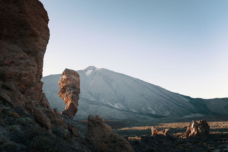 Rock formation in front of volcano against clear sky