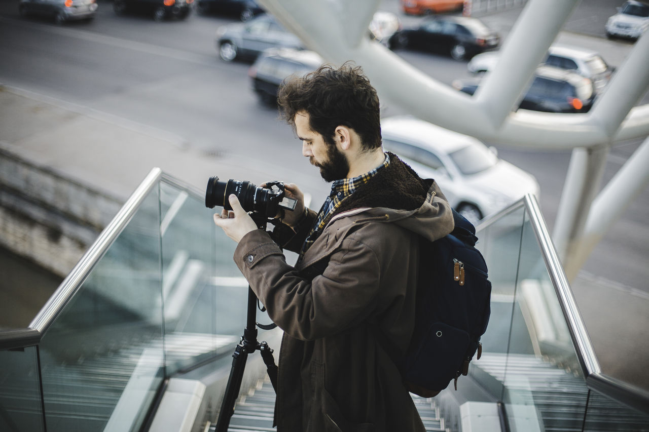 Side view of young man photographing through camera standing on steps